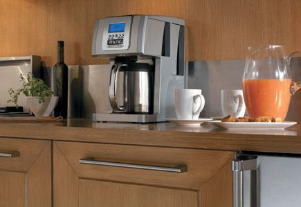 A stainless steel programmable coffee maker in a modern kitchen.