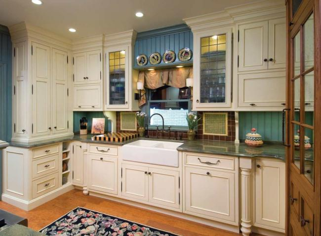 A small Pullman kitchen with yellow painted maple cabinets, granite counters and a tile backsplash