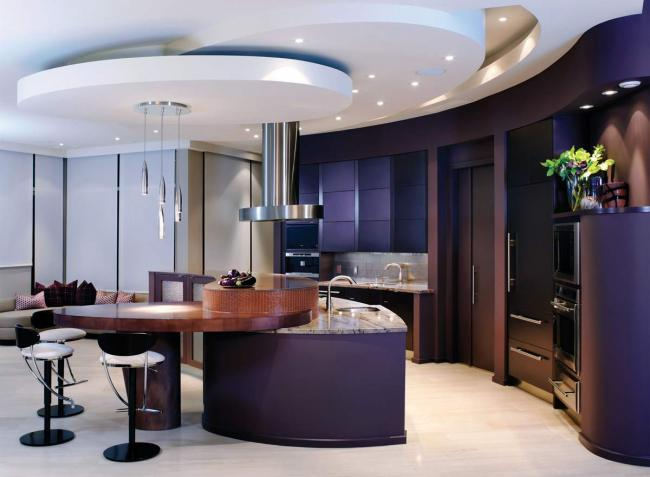 This contemporary kitchen has purple cabinets, purple walls, a limestone floor and granite and wood countertops