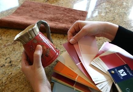 Close up of someone matching color swatches to a small jug