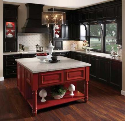 A traditional kitchen with black cabinets and a red island.