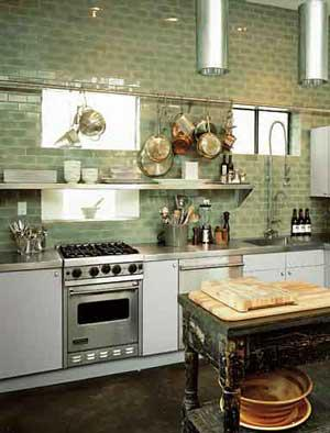 Kitchen with white cabinets and green tile walls.