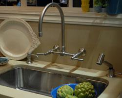 Stainless steel kitchen sink with wallmount bridge faucet.