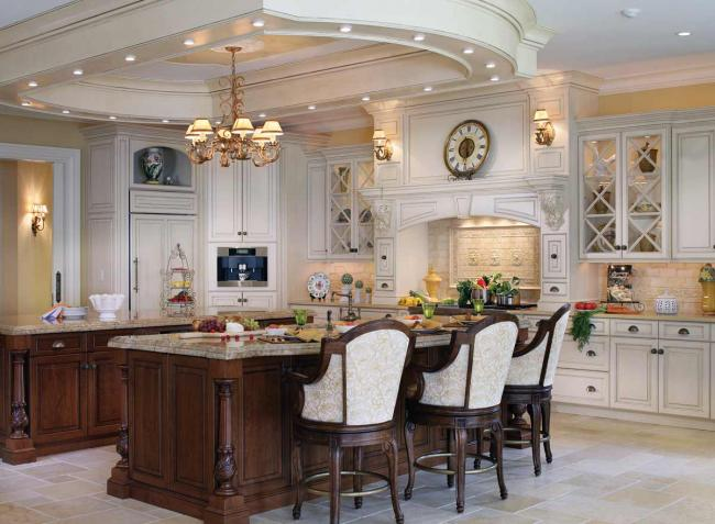 A traditional English manor style kitchen with white cabinets, a large custom range hood, a built-in coffeemaker and two kitchen islands