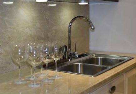 Stainless steel sink with stone counter and backsplash, white cabinets and wine glasses.