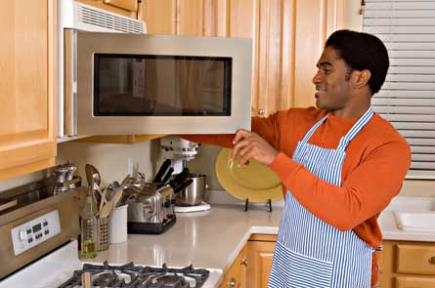 Man using an over-the-range microwave in the kitchen.