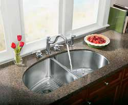 Widespread faucet with undermount stainless steel sink.