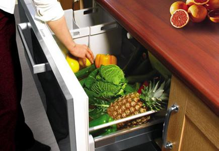 Someone reaching into a drawer full of fruit and vegetables