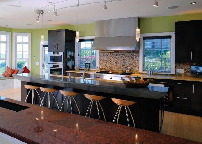 Colorful kitchen with green wall, onyx tile backsplash, double ovens and large rangetop