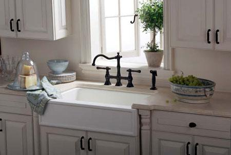 A rustic kitchen pairs an apron sink with a bridge faucet in an oil-rubbed bronze finish.