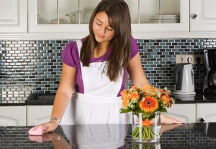 Woman in a black and white kitchen wiping the countertop.