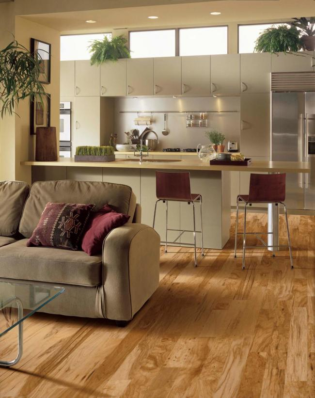 Contemporary white kitchen with hickory flooring open to the living room