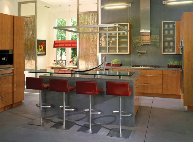 This contemporary kitchen has concrete floors and an island with a glass bar top and red stools