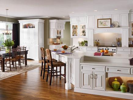 A large classic kitchen with white cabinets and hardwood flooring.