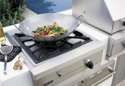 Outdoor side burner with wok next to built-in grill.