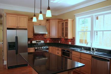 A kitchen with medium brown cabinetry and dark countertops