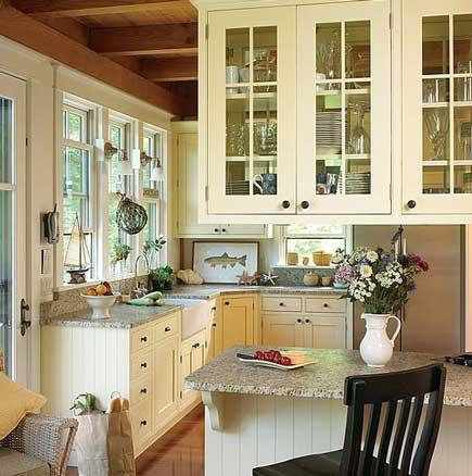 A small country kitchen with yellow cabinets.
