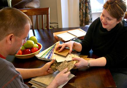 A man and a woman compare tiles samples
