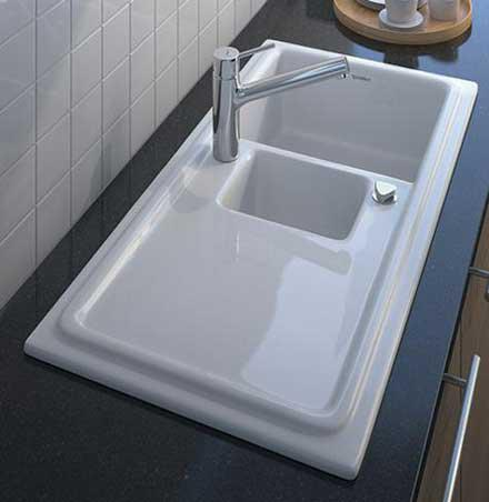 A white kitchen sink with pop-up drain.