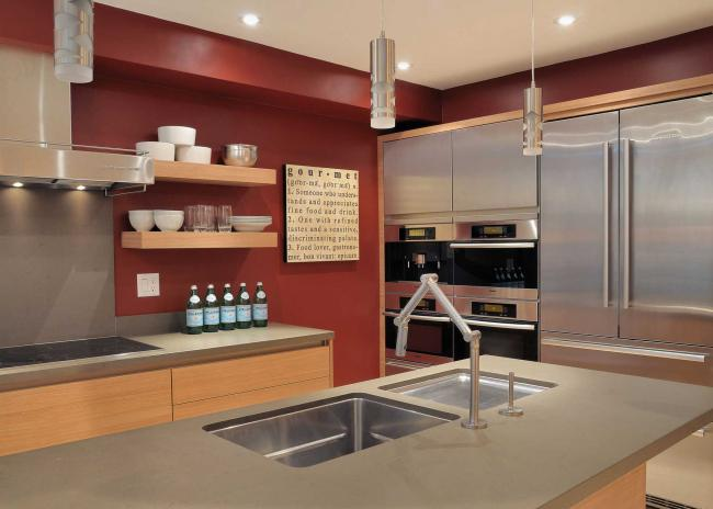 Contemporary kitchen with red wall, stainless steel appliances, gray quartz countertop