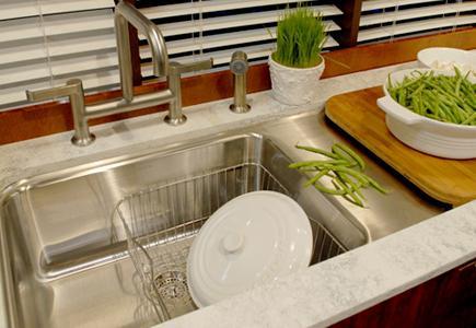Orange undermount sink with dish drainer and granite counter.