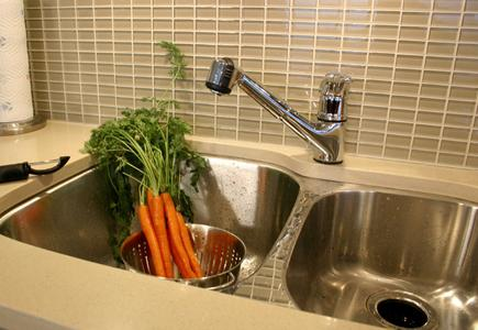 A stainless steel undermount sink with matching faucet.