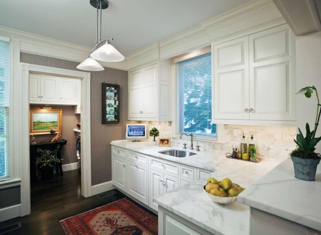 A classic kitchen with white cabinets, marble counters and crystal knobs