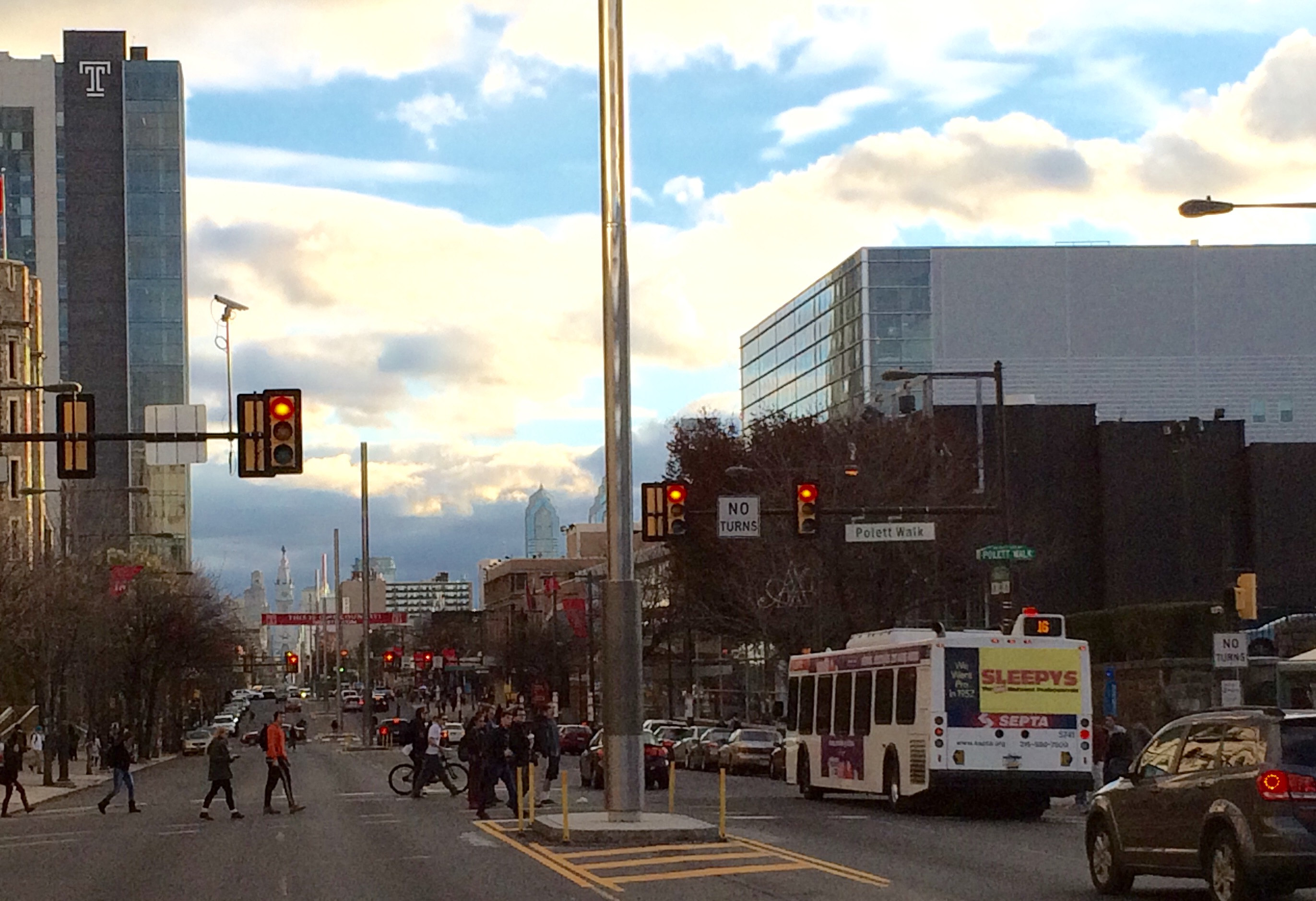 Students walk across Broad Street, passing by the new light poles