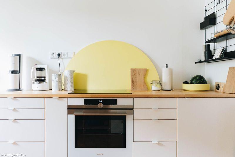 Lackierte Holzplatten als Spritzschutz für die Küche.