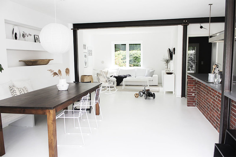 Wohnzimmer und Küche mit Wänden ganz in Weiß.