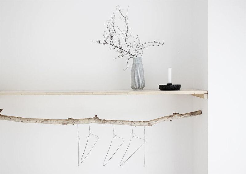 Dekoelemente aus Holz vor einer Wand in Weiß.