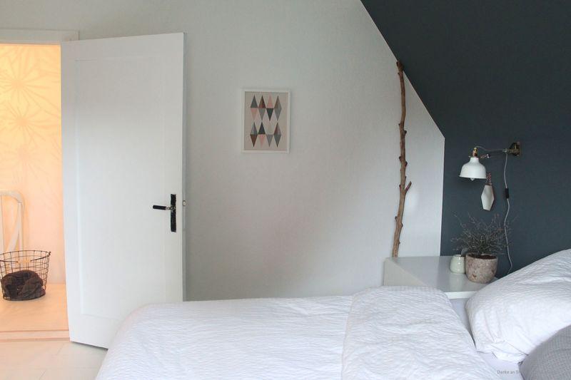 Schlafzimmer mit einer Wand in Dunkelgrau.