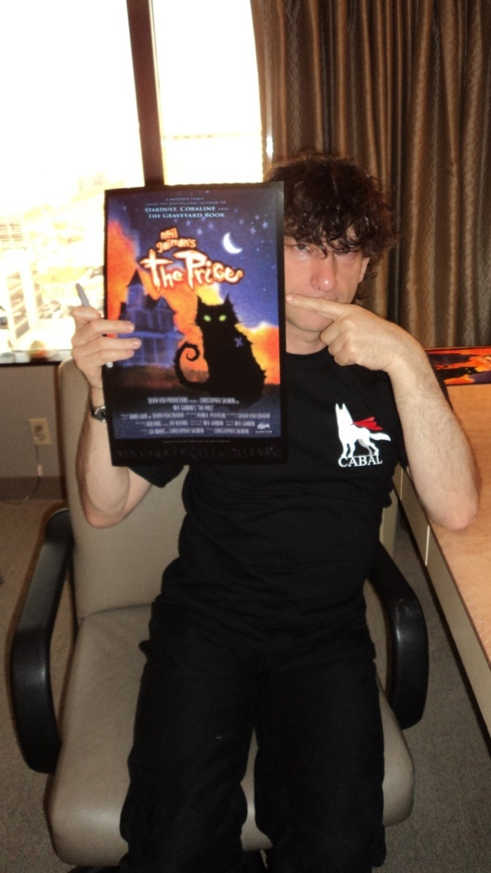 "Neil Gaimen, holding a copy of the film poster for ""The Price"""