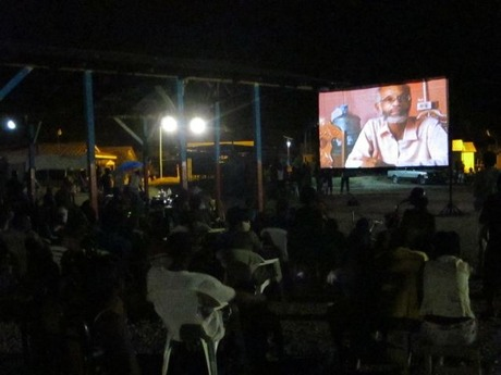 Audience members watch the film on an outdoor screen at Tabarre.