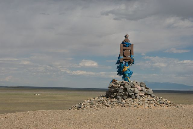 Stone ovoo with a Soyombo, the national symbol of Mongolia, overlooks a Gobi landscape; it is festooned with khadag, blue offering scarves