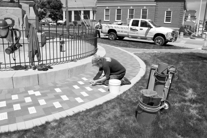 A worker adds names to a war memorial in Geneva, Ohio.