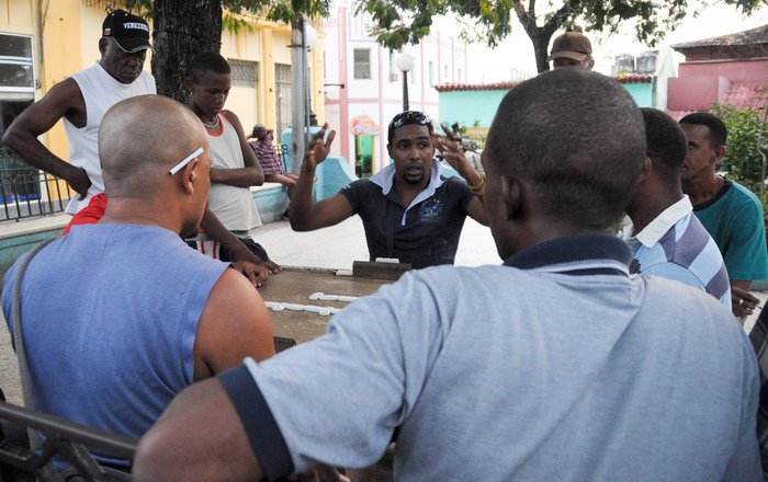 A group of men playing a lively game of dominoes in the Parque Serrano in Santiago de Cuba.