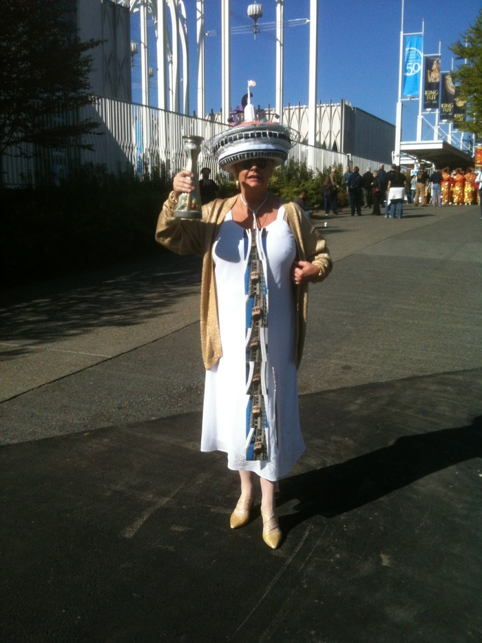 A fan celebrating the 50th birthday of the Space Needle this year. Behind her is the Pacific Science Center, originally the United States Pavilion at the 1962 Seattle World's Fair.