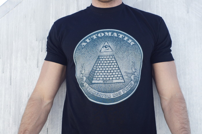 The Seal of Automatik. Levantum Nos Fides translates to In Comfort We Trust. Shirt is a black cotton blend.