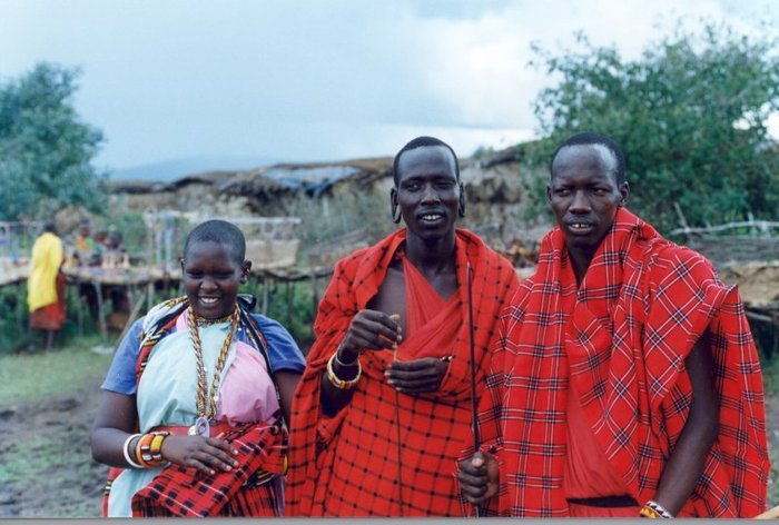The woman is holding a folded Masai blanket, and the men are each wearing blankets. I often wear one of these lightweight blankets when sitting around a campfire on a chilly night.
