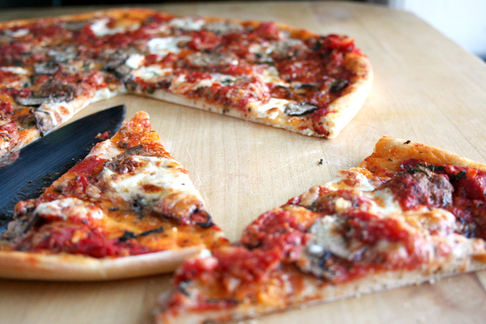 Thin-crust pizza made with kimchi, mushrooms, and sausage