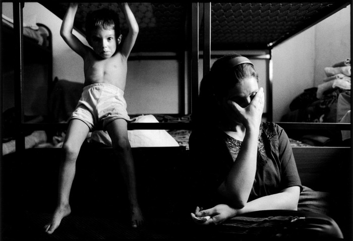 Sebanate Berisha, a Kosovar Albanian refugee who lost all of her children in a night-time bombing raid in Kosovo, at a refugee center with an unidentified boy. Tirana, Albania, 1999.