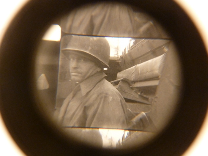A photo taken, through a loupe, of a frame from one of Sam's 16mm film WWII-era films currently awaiting funding for a digital transfer