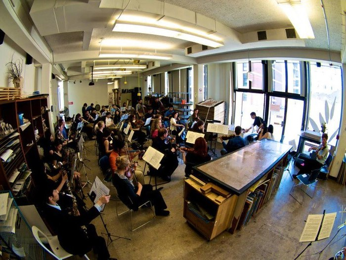 Orchestra performs in an art studio