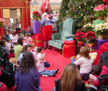 Santa, in his workshop outfit, reading to children at Northpark Mall, Ridgeland, MS