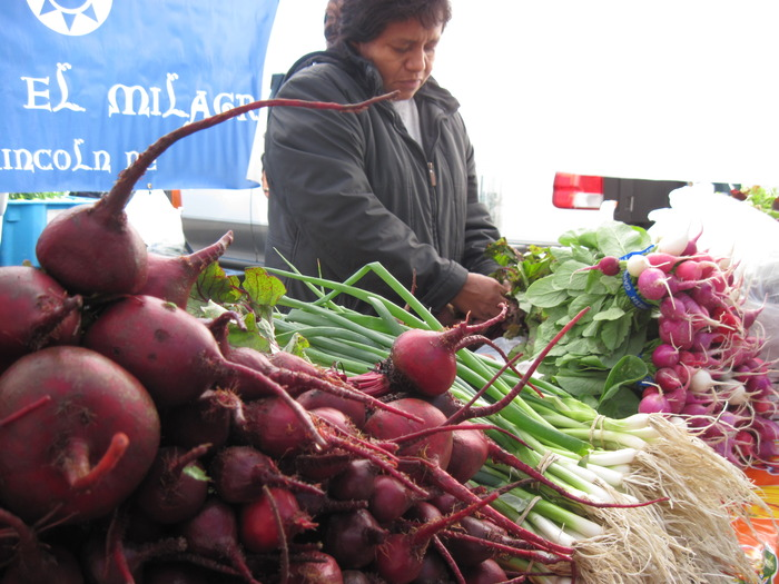 Program graduate Enriqueta bunches beets at her farmers' market stall