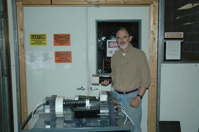 Figure 6: Dr. Witherspoon holds a 15cm long plasma accelerator similar to that seen in the photo above showing size comparison between a thruster and a group of three of our high performance single shot accelerators.
