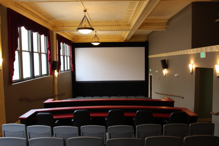 The view from the back of our auditorium showing the 20-foot screen and historic architecture. Blackout curtains cover the windows during theatrical presentations.