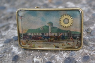 A belt buckle (Antiqued Brass) made with a vintage 1973 Mississippi tourism brochure (Reward level $35)
