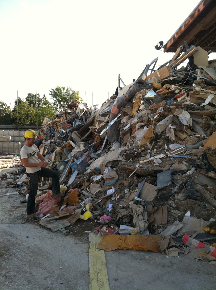 Artist Billy Blaise Dufala scoping the piles of waste for materials.